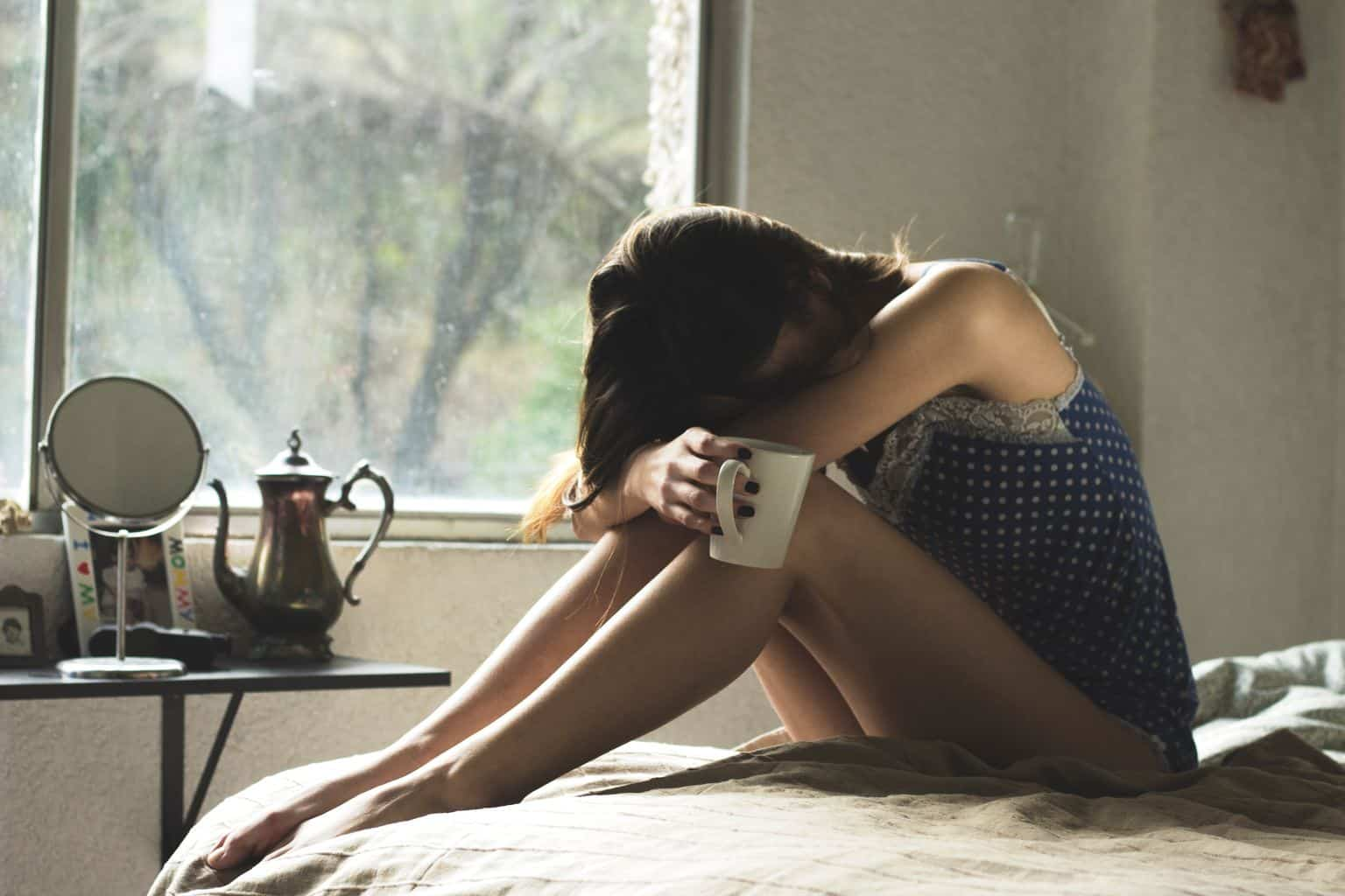 depressed woman sitting on the bed, holding a mug