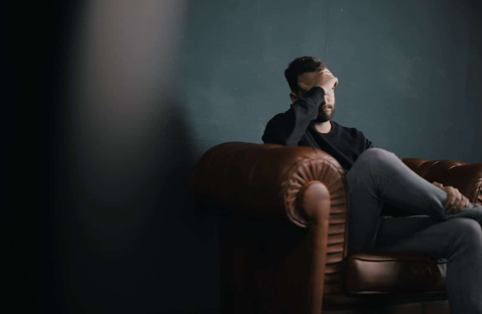 man suffers headache sitting on a sofa