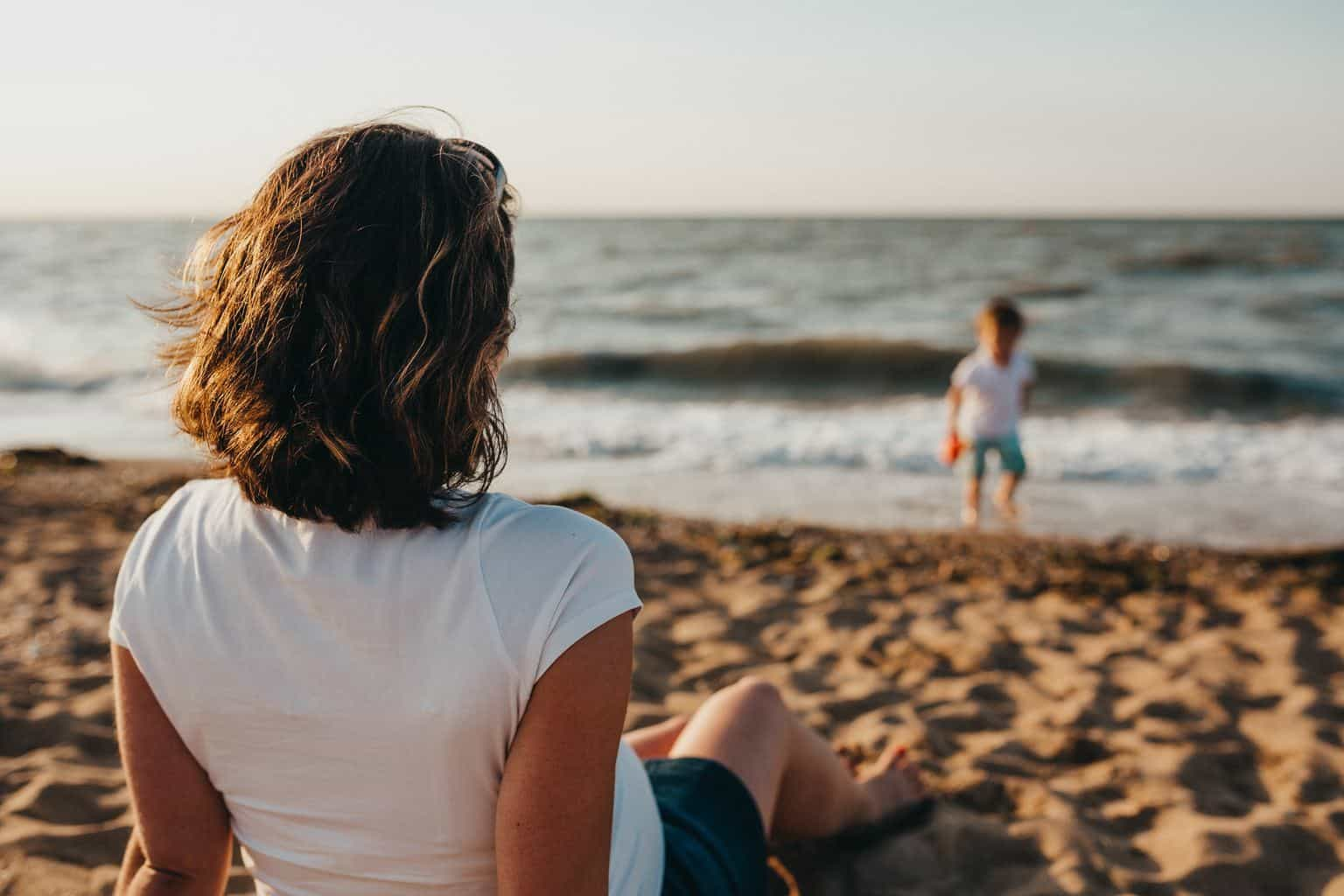 woman watching child playing on beach during daytime